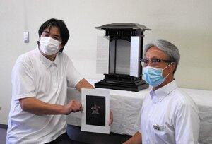 厨子の内面に浮かぶ文字「空」をイメージした紙を持つNao漆工房の小畑社長(左)と、ナンゴ-の南郷社長=宇治市宇治・市役所