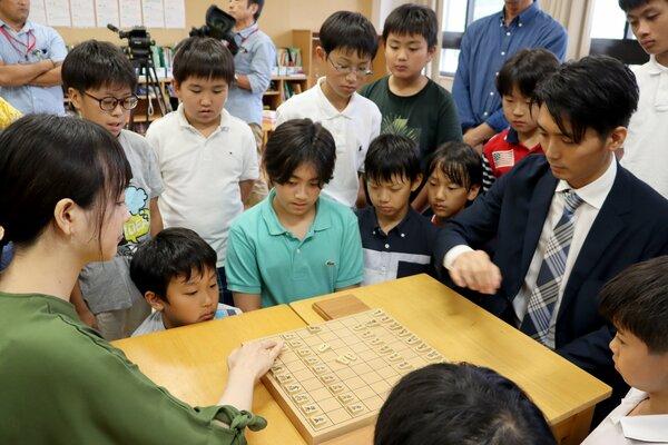 プロ棋士による対局を通して、駒の並べ方や礼儀作法などを学ぶ児童ら(京都市左京区・同志社小)