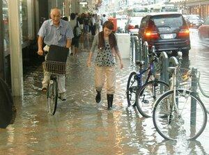 大雨で冠水し、川のようになった歩道を通る人たち(2013年8月5日午後3時55分、京都市下京区四条通富小路西入ル)