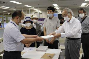 仁和寺前のホテル建設計画について手続きの中止を京都市職員(左)に申し入れる住民ら=中京区・市役所
