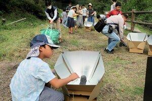 太陽光を集める箱に黒い缶に入れた水を置いて温める子どもら(精華町精華台・けいはんな記念公園)