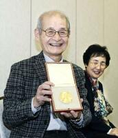 ノーベル賞の授賞式から帰国し、記者会見でメダルを披露する吉野彰・旭化成名誉フェロー。右は妻久美子さん=15日午前、成田空港