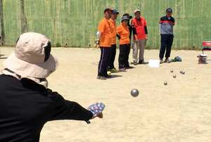 オレンジ色の目標球に向かってボールを投げる府知事杯ペタンク大会の参加者(京都府亀岡市宮前町・市国際広場球技場)