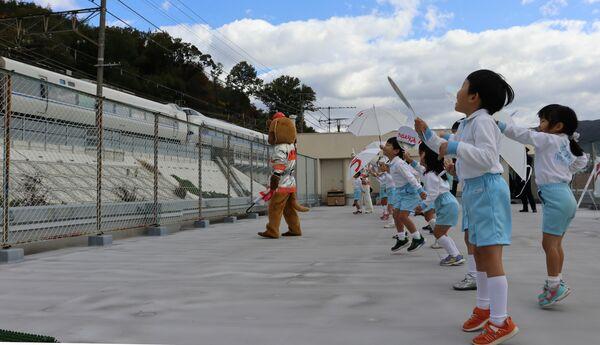 近くを通過する電車の乗客に向かって防火を呼びかける子どもたち(京都市山科区・寺西幼稚園)