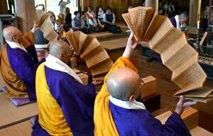 転読法要で、両手で経典を扇のように開く僧侶ら(京都府綾部市睦寄町・光明寺)