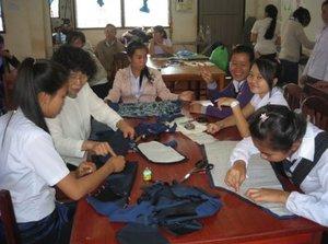 NPO法人「リボーン・京都」メンバーから洋裁を教わるラオスの女性たち(同法人提供)