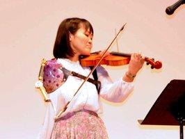 義手を使ってバイオリンを演奏する伊藤さん(八幡市八幡・市文化センター)