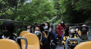 シャトルバスの試乗会で、頭上の風景を楽しむ関係者ら(10月19日、京都市右京区)