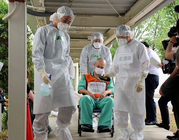 新型コロナウイルスへの対応訓練で、感染した疑いのある受刑者役(中央)を隔離する防護服姿の刑務所職員ら=京都市山科区・京都刑務所