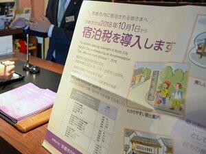 旅館の受付に掲示された宿泊税導入を知らせるポスター(2018年10月)