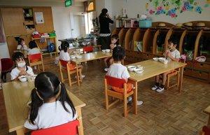 給食の時間に間隔を空けて座る園児たち。食べる直前までマスクは外さない(京都市伏見区・桜木こども園)
