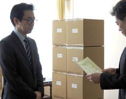 マスク1万枚を寄贈した遠藤社長(左、京都府向日市役所)