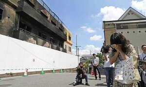 放火から1週間。「京都アニメーション」第1スタジオの前で顔を覆う女性(25日午前10時56分、京都市伏見区桃山町)