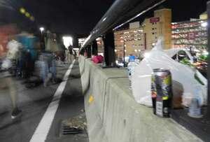 保津川市民花火大会で来場者の帰宅路となった保津橋。レジ袋などのごみが散乱していた(11日午後9時半ごろ、京都府亀岡市保津町)
