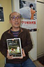 土屋トカチ監督と、上映が始まったドキュメンタリー映画「アリ地獄天国」のポスター(右上)=横浜市内
