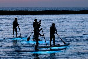 LEDライト付きのボードで夕暮れの海を楽しむSUP(京丹後市網野町・夕日ケ浦海水浴場)=市観光公社提供