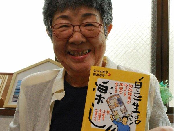 本を手にする佐々木和子さん。「元治は自立生活で自由や自信、達成感を得ている」と話す