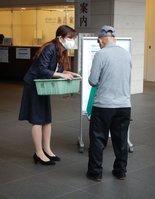 区役所を訪れた高齢者にワクチン接種の予約方法を伝える職員(20日午前9時、京都市右京区役所)