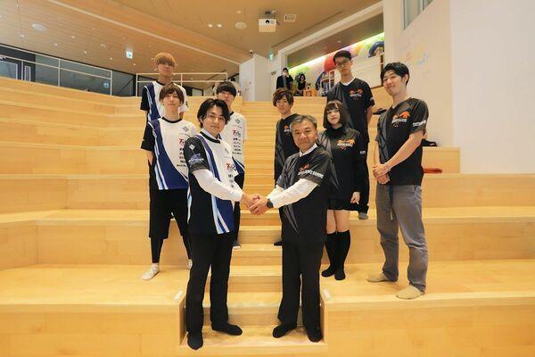 京滋企業のeスポーツ対抗リーグ創設に向けて握手する「SUZAKU GAMING」運営会社の橋本社長(前列右)と、「LAKE GAMING」の清水代表(京都市中京区)