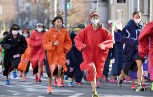 たすきを待つ間、マスクをつけて体を動かす選手たち(京都市北区・第3中継所)