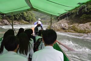 船頭の説明を聞きながら川下りを楽しむ生徒たち(京都府亀岡市)