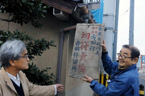 「城陽の緑と文化財を守る会」が、芦田さん(右)宅で見つけた奈良電鉄バスの停留所看板=城陽市寺田