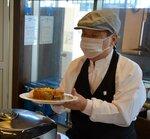 できあがったカレーを客に差し出す中嶋さん(滋賀県米原市・IZUTSUYAカレーのお店)