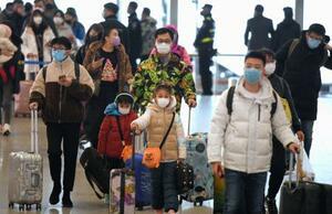 マスク姿の旅行客ら=24日、北京首都国際空港(共同)