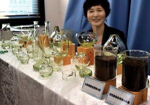 琵琶湖の水草を色の原料にした初めてのガラス工芸品を紹介する神永さん(大津市・県庁)