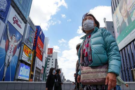 新型コロナウイルスの影響による外出自粛要請のため、人通りが少ない大阪・道頓堀で、マスクを着けて歩く人=5日午後