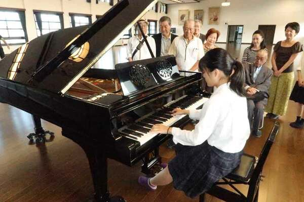 修復が終わり、講堂に戻ったピアノの音色に聴き入る鴨沂高OBら(京都市上京区・同高)