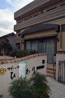 昨年8月に閉鎖したマザーハウスひまわり。建物は売却され、塀には宿泊施設になることを告げる紙が貼られている(京都市西京区)