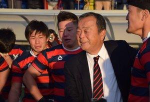 試合終了後、グラウンドで選手たちをねぎらう京産大の大西監督