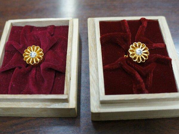 京都市議全員に支給されている22金製の議員バッジ(左)。右は今後使用する金メッキ製のバッジ