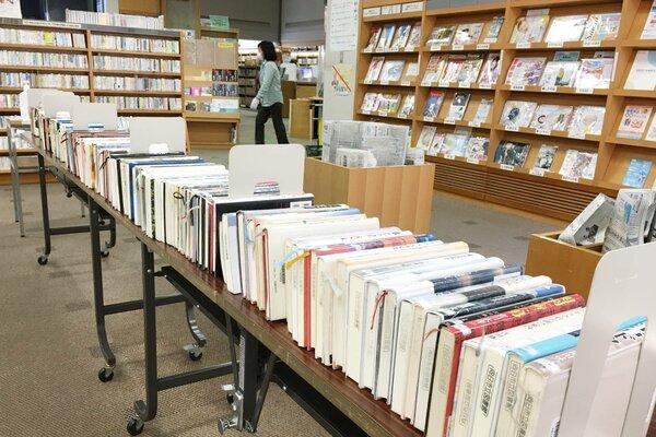 休館中の返却などで、本棚に入りきらなくなった書籍。長机や棚を置くなどして、配架スペースを確保している(向日市図書館)