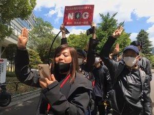 5月に東京で行われた国軍への抗議デモで、抵抗の意味を表す3本指を掲げるスェイさん(手前)=ユーチューブ番組から