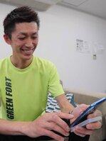 スマートフォンで「LINE回覧板」を操作する安田会長(京都府長岡京市)