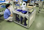 ハムスが開発しているマスク製造装置の試作機。アームの先端の刃で生地をマスクの形に裁断する