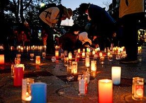 犠牲者の慰霊と被災地復興への願いを込めたキャンドルに火をともした参加者たち(2018年3月10日、京都市伏見区・向島ニュータウン)