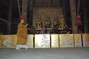 仏殿の内陣に展示された金箔の作品と読経する僧侶(京都市東山区・泉涌寺)