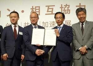 協定を交わして握手する西脇知事(中央右)と郭会長=東京・丸の内