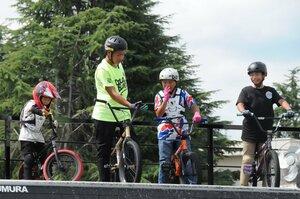 自身の練習時間中も、子どもたちに助言する高橋さん(左から2人目)=向日市・京都向日町競輪場。講座でも基本動作を丁寧に説明する