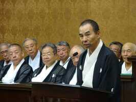 議場であいさつする鷹山保存会理事長の山田さん