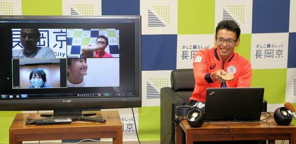東京五輪の銅メダルを画面にかざす山西選手(右)と、笑顔を見せる対談した市民ら=長岡京市役所