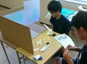 厚紙で船などを手作りして撮影の準備を進める学生(京都府舞鶴市白屋・舞鶴工業高等専門学校)=舞鶴高専提供