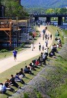 緊急事態宣言が発令された初日、鴨川沿いで並んで座る若者ら(25日午後2時35分、京都市中京区)