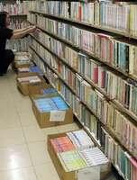 本の入った段ボール箱が床に置かれた宇治市中央図書館の書庫。書架の段数も増やし、ぎっしりと詰められている(京都府宇治市折居台)