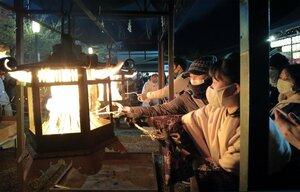 灯籠から縄に火を移す参拝者(31日午後7時15分、京都市東山区)