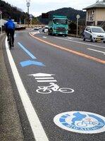 ビワイチのルート上。ロゴマーク(手前)と青破線、矢羽根マークが連続して示されている場所もある(滋賀県近江八幡市島町・さざなみ街道)