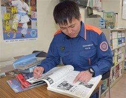 震災を報じる新聞記事を眺める吉元さん。自宅近くの病院が写真に写っていた